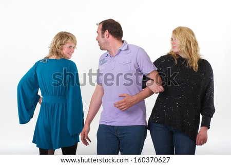 Man is walking with his wife or girlfriend arm in arm. They pass a woman and he turns his head and looks at her. The other woman is smiling and flirting with him and his wife or girlfriend is jealous. - stock photo