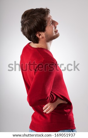 Man isolated in red sweater suffering from strong back pain - stock photo