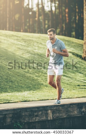 Man jogging. Full length of confident young man running along quayside - stock photo