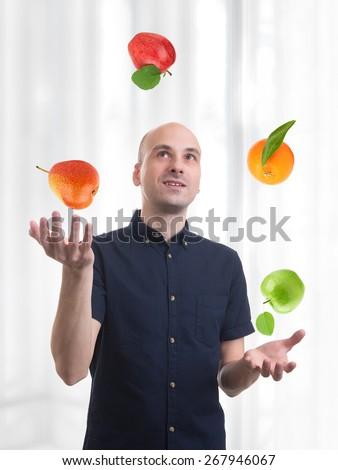 man juggle fruits. Apple, orange and pear - stock photo
