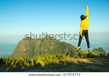 Man Jumping Celebrating Success with the view of a Mountain (Pico Parana - Brazil) - stock photo