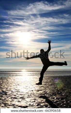 Man jumping high on the seashore - stock photo