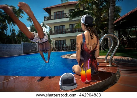 Man jumping in swimming pool and his girlfriend take a rest at resort. Low angle view from the swimming pool. - stock photo