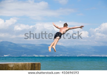 Man jumping off cliff into the sea. Summer fun lifestyle. - stock photo