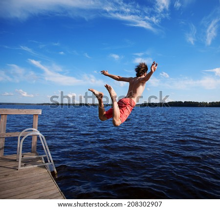 Man jumping off jetty. - stock photo