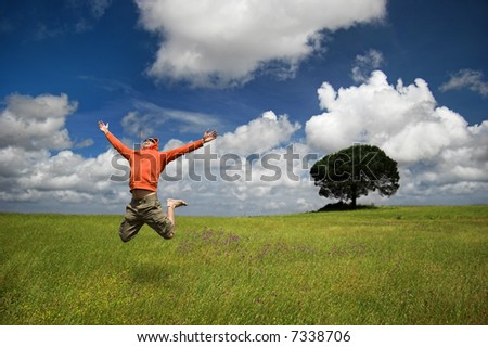 Man jumping on a green meadow with a beautiful cloudy sky - stock photo