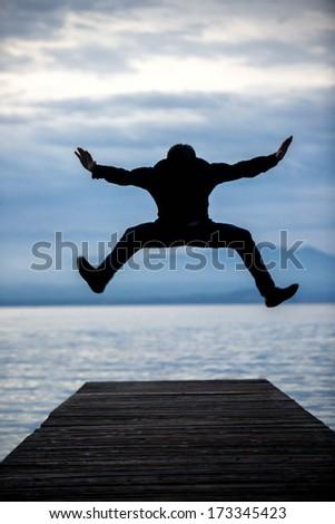 Man jumping on an empty footbridge in dawn - stock photo