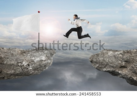 Man jumping on cliff with blank white flag and natural sunlight cloudscapes background - stock photo