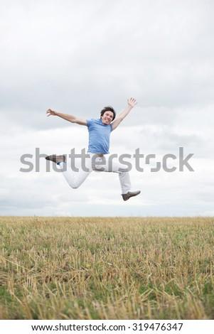 Man jumping on the autumn field - stock photo