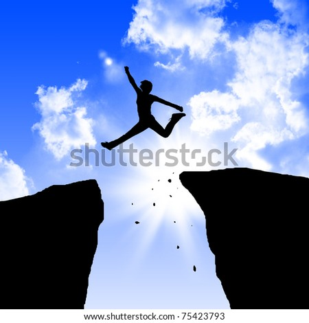 man jumping on the rocks against blue skymountain - stock photo
