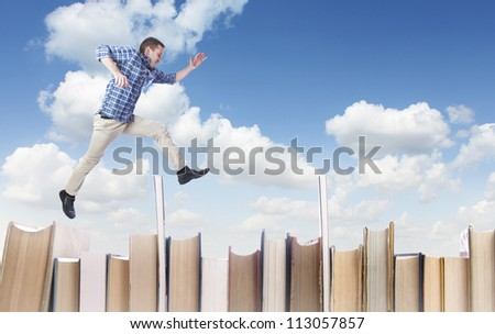 Man jumping over books - stock photo