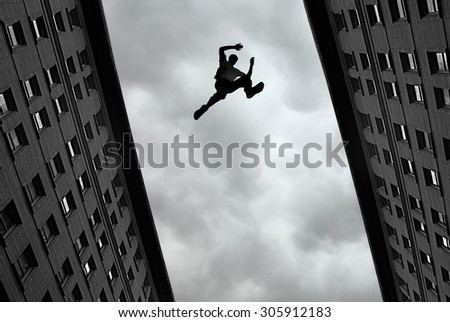 Man jumping over building roof against gray sky background - stock photo