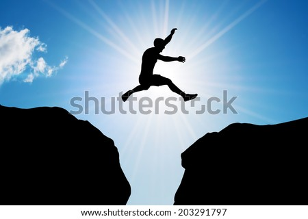 Man jumping over precipice between two rocky mountains at sun light. Freedom, risk, challenge, success. - stock photo