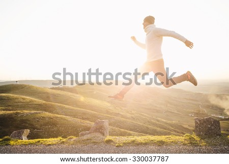 Man jumping over precipice between two stones on mountains at sunset - stock photo