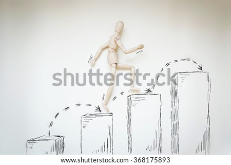 Man jumping up higher from step to step. Abstract image with wooden puppet - stock photo