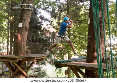 Man jumping while climbing in high rope course - stock photo