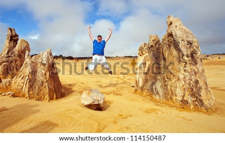 Man jumps in Pinnacles Desert, Australia - stock photo
