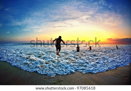 Man jumps over a wave during sunset on beach in Costa Rica - stock photo