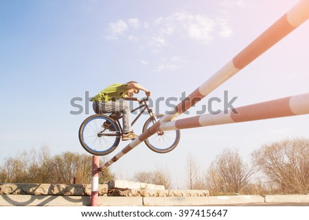 Man jumps over the barrier on stunt bike. Such jump on a bike called the Bunny Hop.  - stock photo