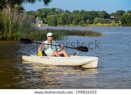 Man kayak fishing  - stock photo