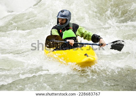 Man kayaking down class IV Boulder Drop rapid on the Skykomish River in Washington State.  - stock photo