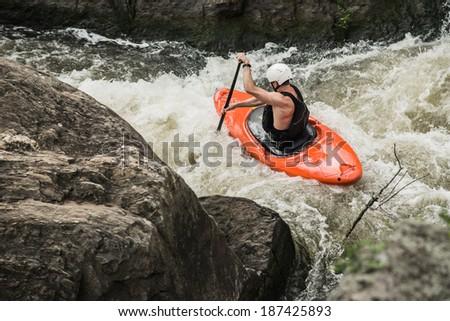 Man kayaking down whitewater - stock photo
