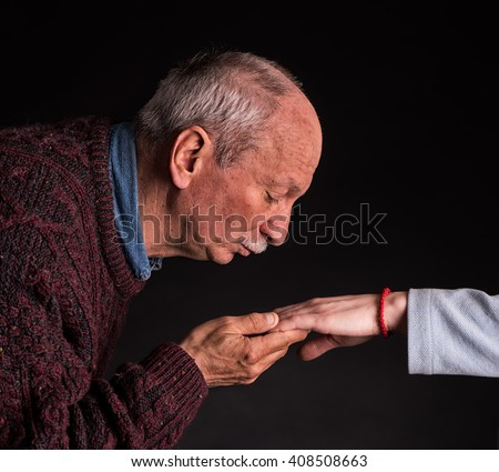 Man kissing woman's hand on a dark background - stock photo
