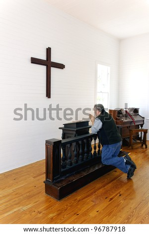 Man kneeling and praying in front of a cross at a church. - stock photo