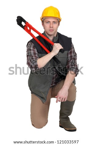 Man kneeling with bolt-cutter - stock photo
