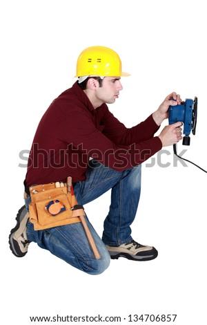 Man kneeling with power sander - stock photo