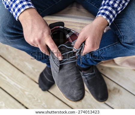 Man lacing his suede shoes,sitting on chair at home - stock photo