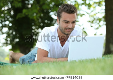 Man laid in field with laptop computer - stock photo