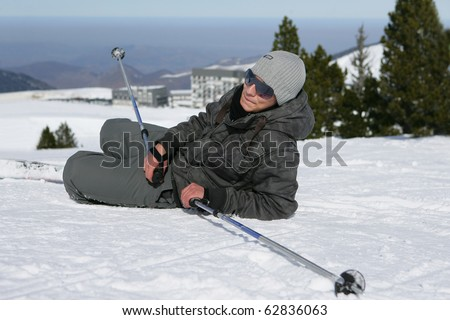 Man laid in snow with skis - stock photo