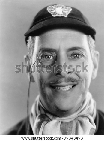 Man laughing and a monocle and a cap in his head - stock photo
