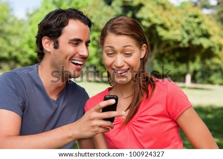 Man laughing as he shows something on his phone to his friend who is laughing happily while sitting in a bright grassland - stock photo