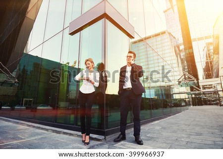 Man lawyer is having mobile phone conversation, while his client is checking time before start court session. Male entrepreneur is calling with cell telephone, while is standing with partner outside - stock photo