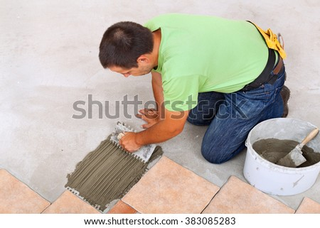 Man laying ceramic tiles floor, spreading the adhesive on the concrete - focus on hands - stock photo
