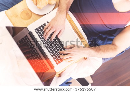 Man laying in bed and using laptop, top view only hands - stock photo