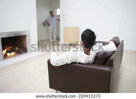 Man laying on sofa looking at man standing in hallway - stock photo