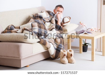 Man laying on sofa uder natural woolen blanket with tissue in his hand  - stock photo