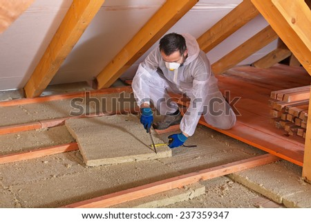 Man laying thermal insulation layer under the roof - using mineral wool panels - stock photo