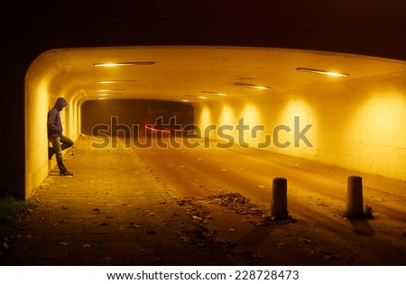 Man leaning against the wall of tunnel on a foggy night while cyclists pass. - stock photo