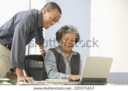 Man leaning over desk of mature woman with computer - stock photo