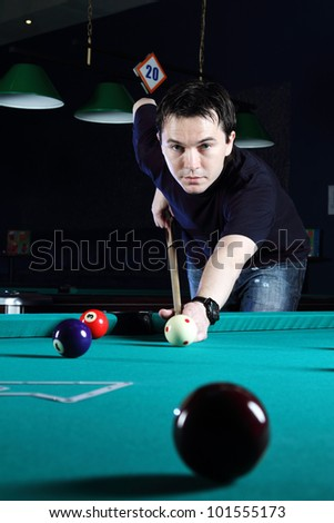 Man learning to play snooker in the dark club. - stock photo