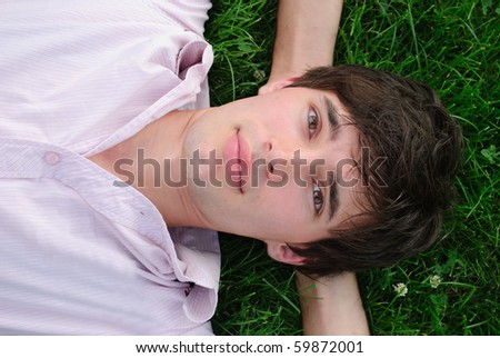 Man lie on the grass and look up. Shallow DOF. Outdoor portrait - stock photo