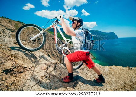 Man lifted the bike up the hill. Mountain Biking.Traveling by bicycle on the outdoors. - stock photo