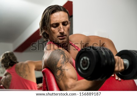 Man Lifting Dumbbell In Gym - stock photo