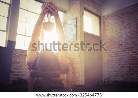 Man lifting dumbbell lying on the bench at the gym - stock photo