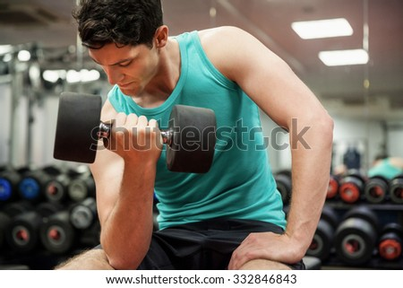 Man lifting dumbbell weight while sitting at the gym - stock photo