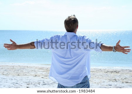 Man lifting his arms out to sides looking at ocean - stock photo
